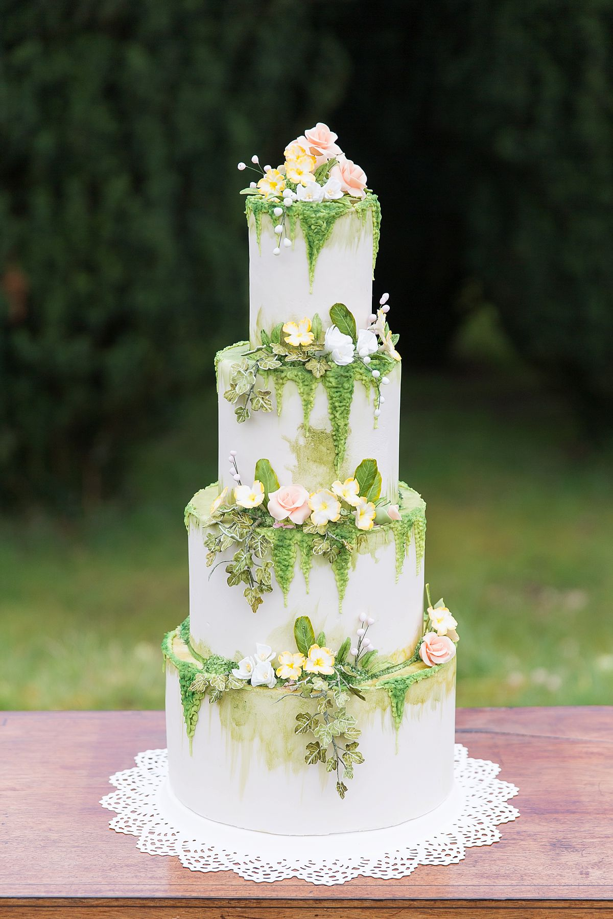 Sugar Mamas classic iced 4-tiers cake with fresh blooms and intricate handmade iced flowers and vines, finished with delicate hand painted detailing.