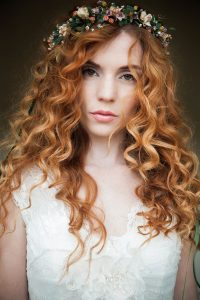 Bride with red curly hair and flower crown for luxury wedding