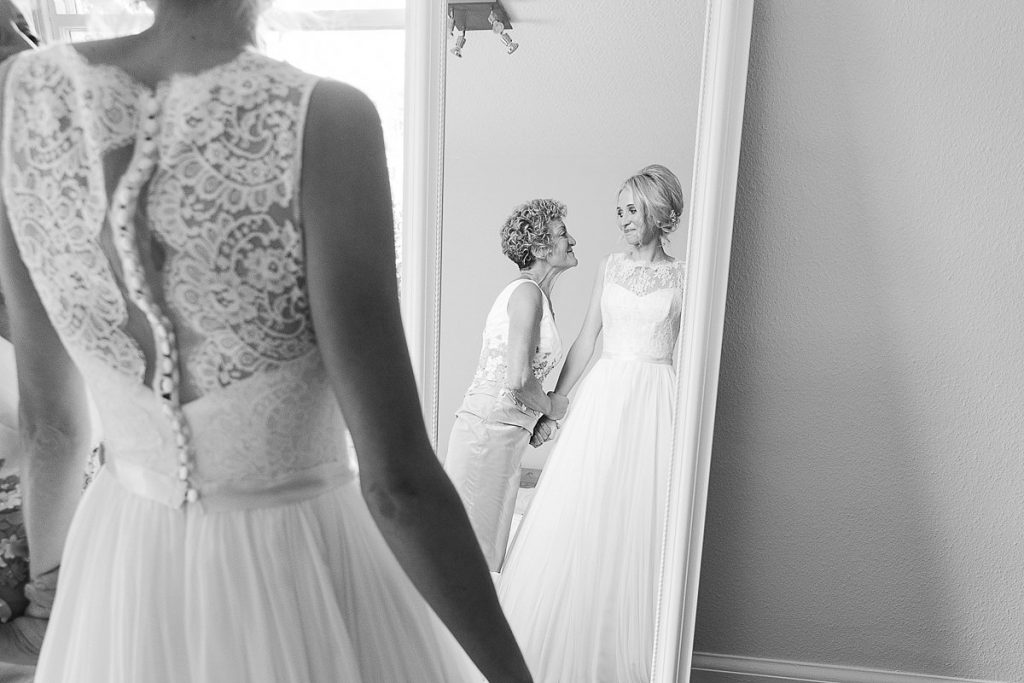 bride and mother look in the mirror at Wiltshire wedding by Mckenzie brown photography