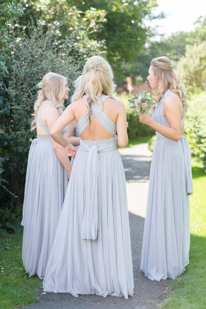 bridesmaids gathered around in pale blue two birds bridesmaids dresses