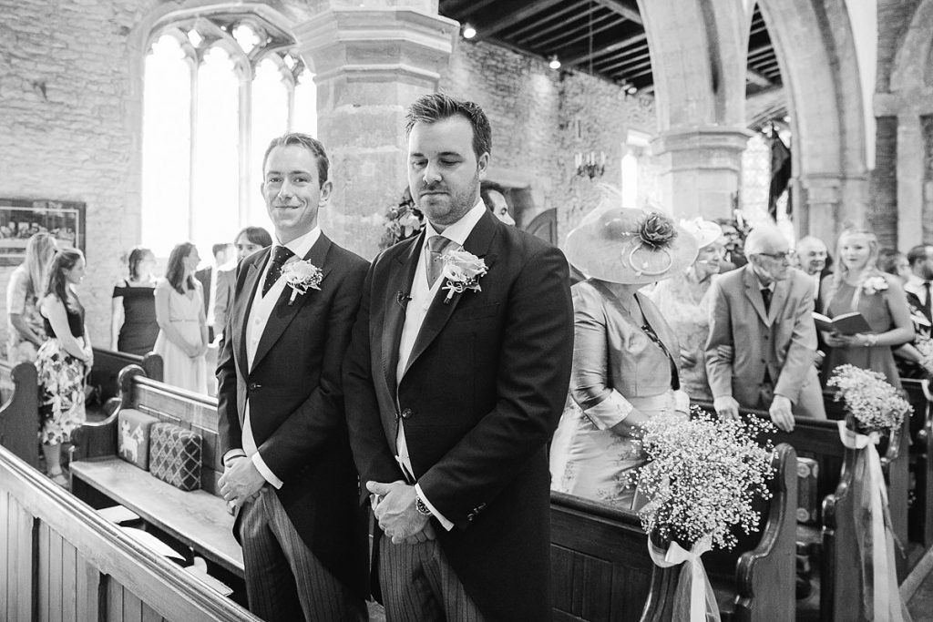 Groom waits patiently for bride at church wedding by wedding photographer Mckenzie brown photography