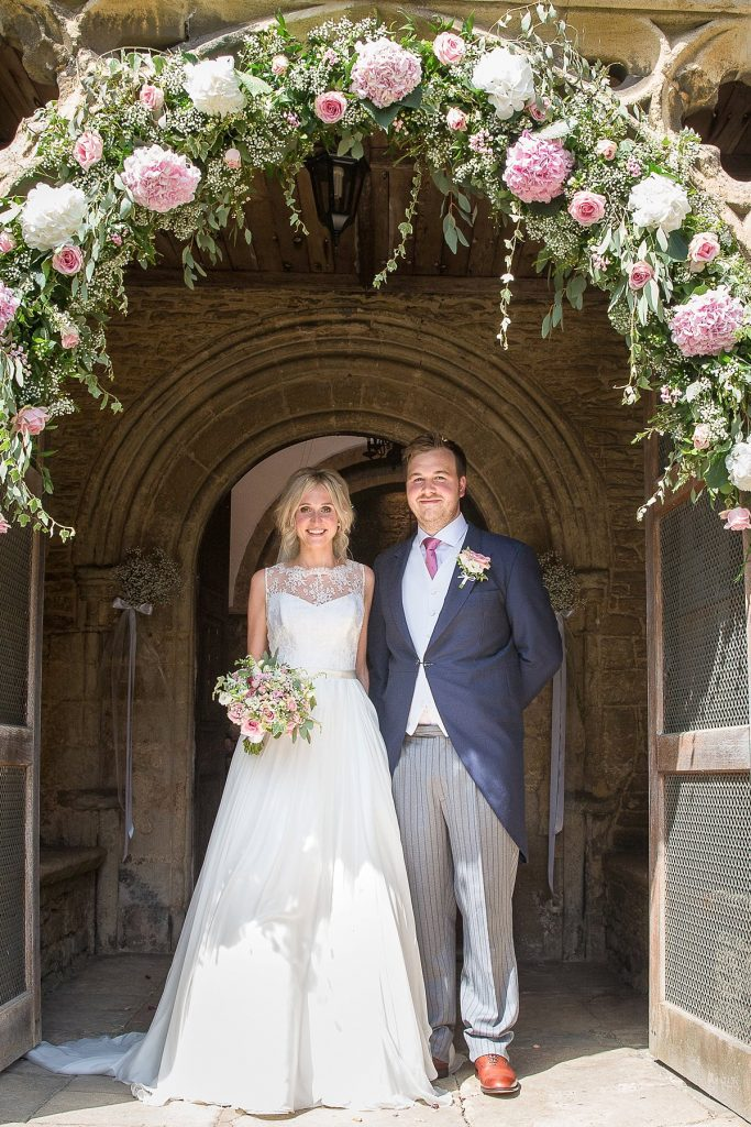 bride and groom stand in doorway of church at Lyveden New Bield by Mckenzie brown photography