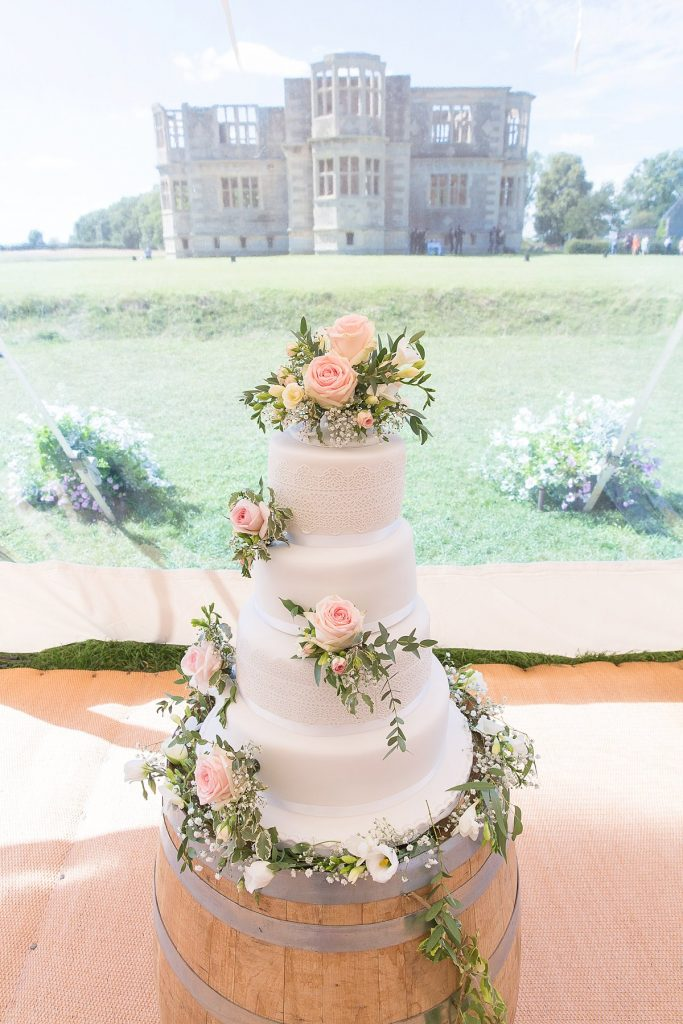 white wedding cake with pink flowers twisting round by Mckenzie brown photography