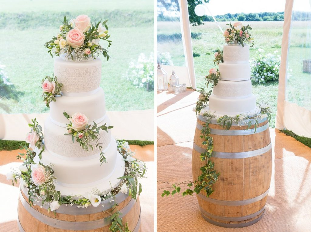 white wedding cake with pink flowers at Lyveden New Bield wedding by Mckenzie brown photography