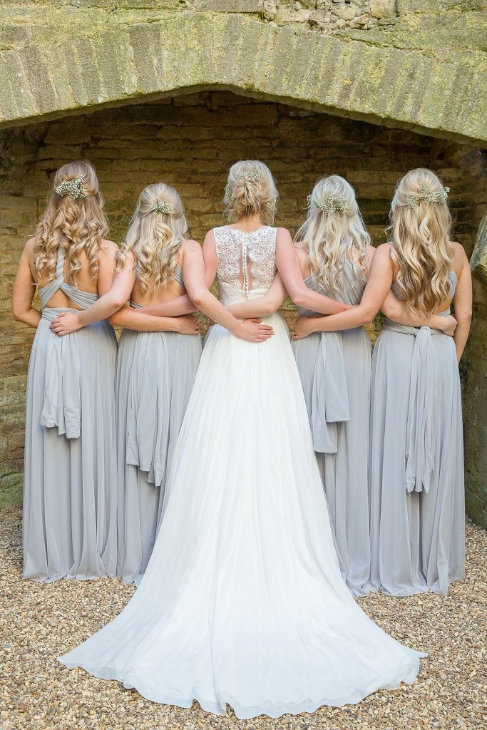 back of bride standing with her bridesmaids at Lyveden New Bield wedding