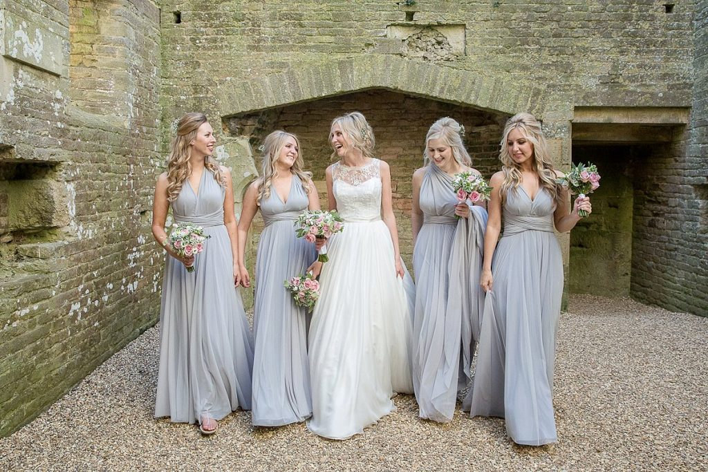 Bride and her bridesmaids walk forward together inside National trust building Lyveden New Bield Mckenzie Brown Photography