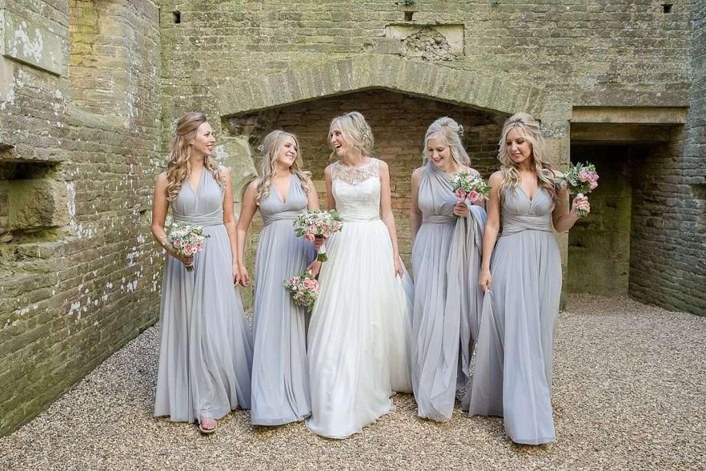 Bride and her bridesmaids walk forward together inside National trust building Lyveden New Bield Mckenzie Brown Photography