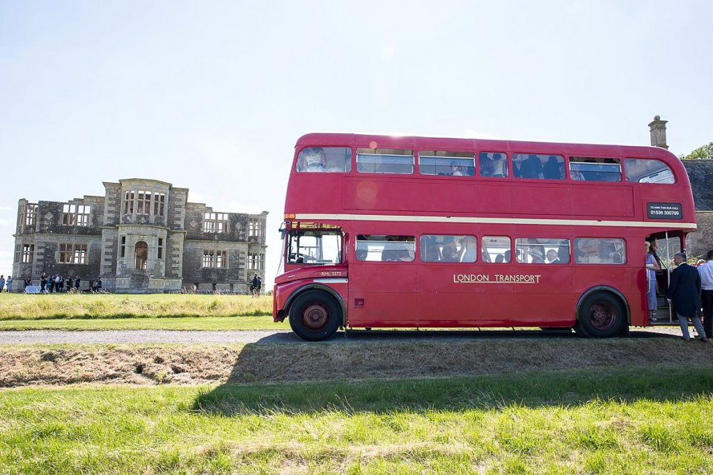 red bus brings wedding guests to Lyveden New Bield
