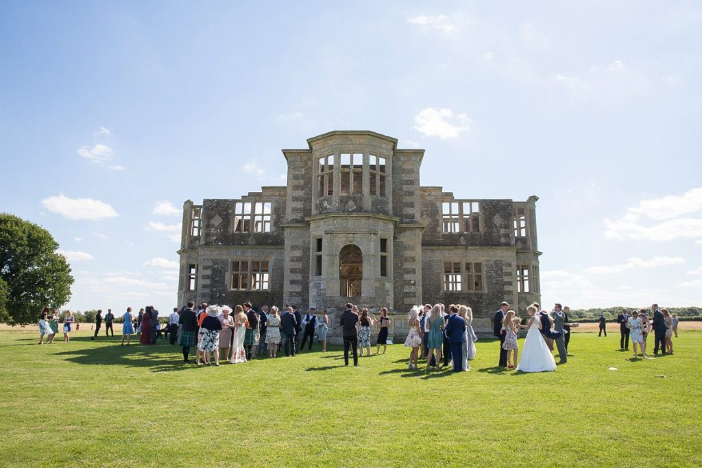 Lyveden New Bield Wedding guests outside the building in summer wedding