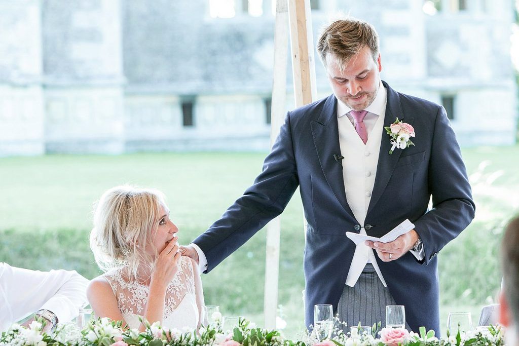 Groom touches bride on shoulder during speeches at Lyveden new bield wedding