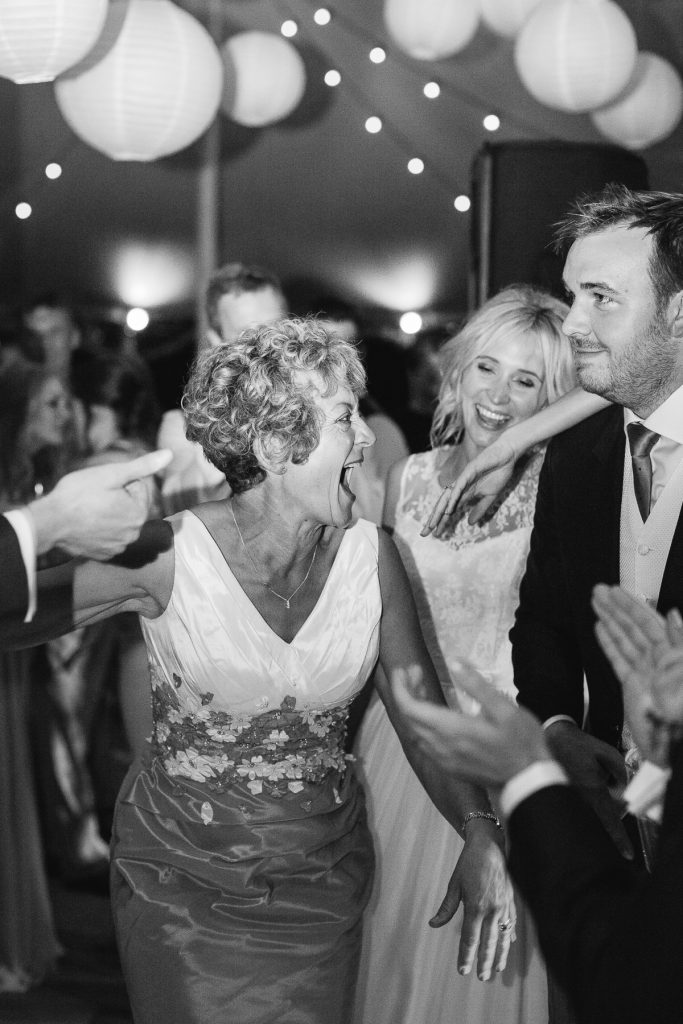 mum laughing with bride at wedding