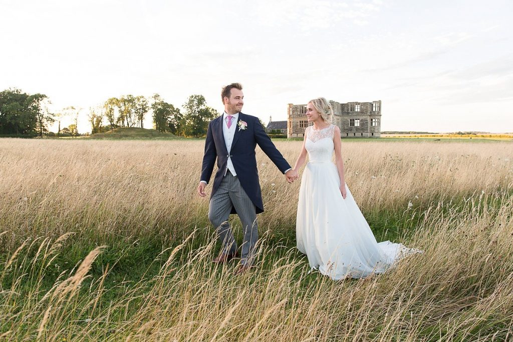 Bride and groom walking in front of Lyveden New Bield National Trust wedding by Mckenzie brown photography