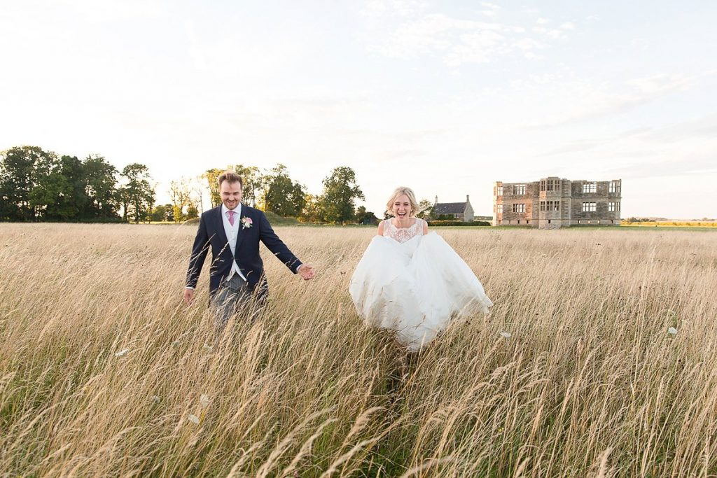 Bride and groom running and laughing in front of Lyveden New Bield wedding by Mckenzie brown photography