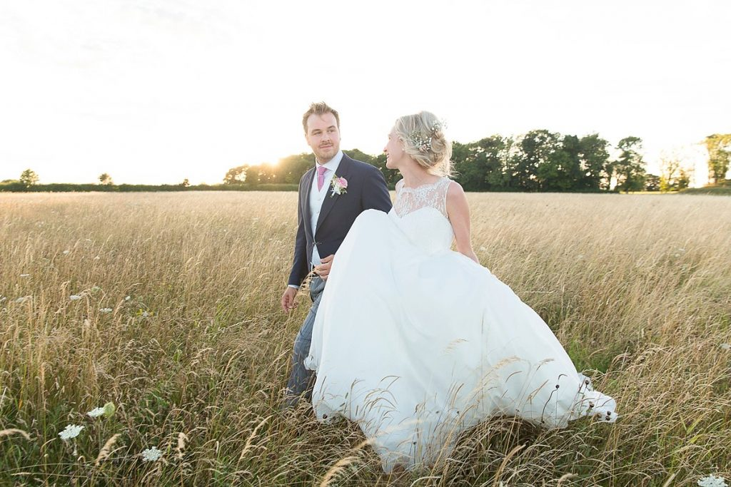 Bride and groom walk at sunset in front of Lyveden New Bield National Trust wedding by Mckenzie brown photography
