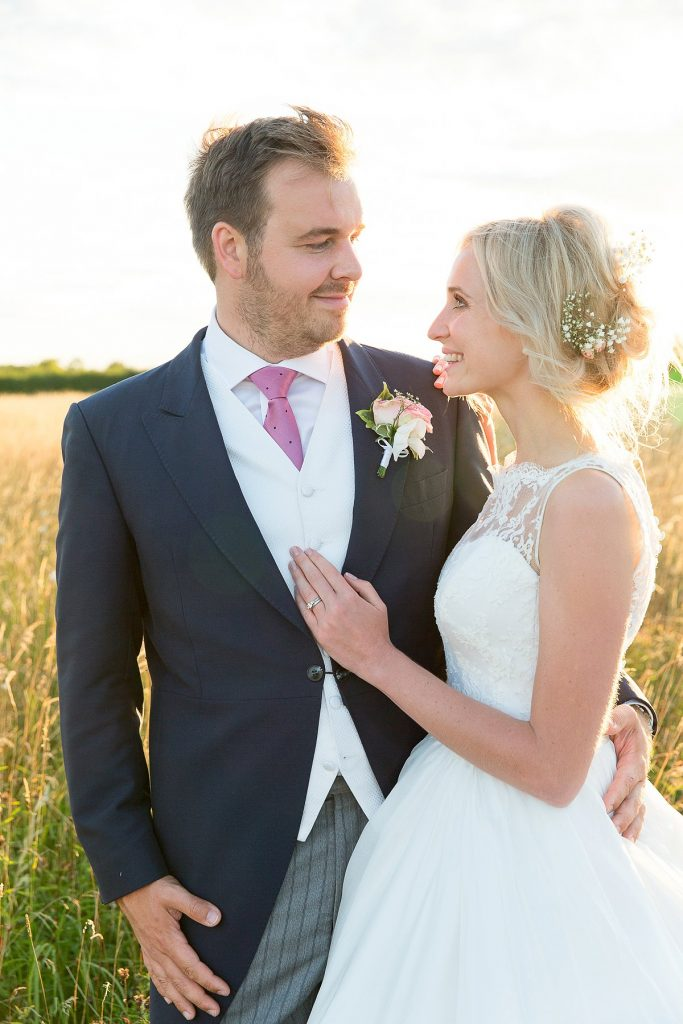 couple smile at each other at Lyveden New Bield National Trust wedding by Mckenzie brown photography
