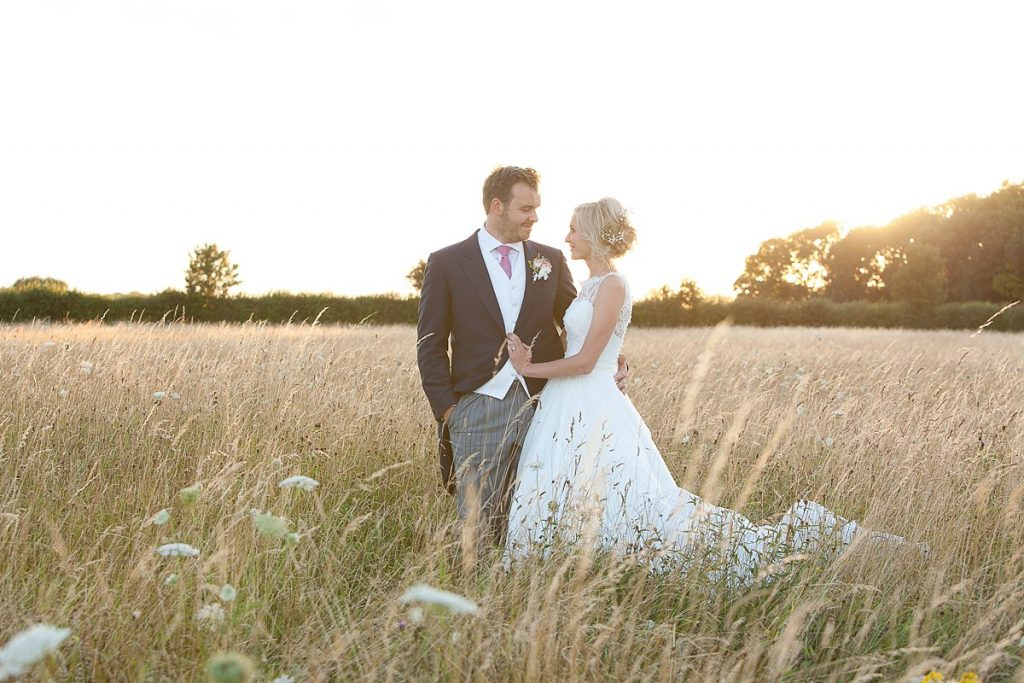 wedding couple in the field at Lyveden New Bield wedding as sun sets behind