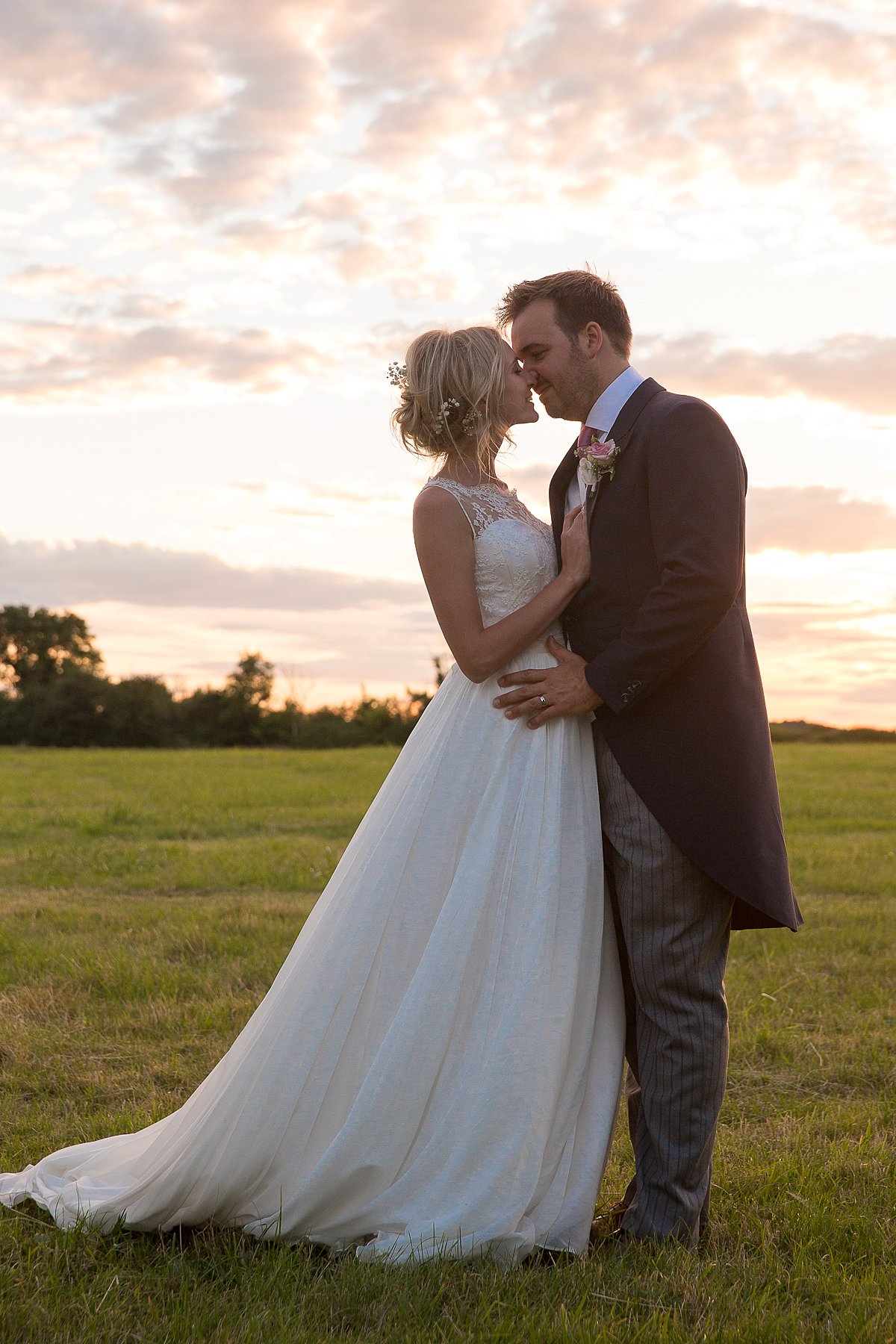 Bride and groom kiss at sunset at Lyveden New Bield National Trust wedding by Mckenzie brown photography