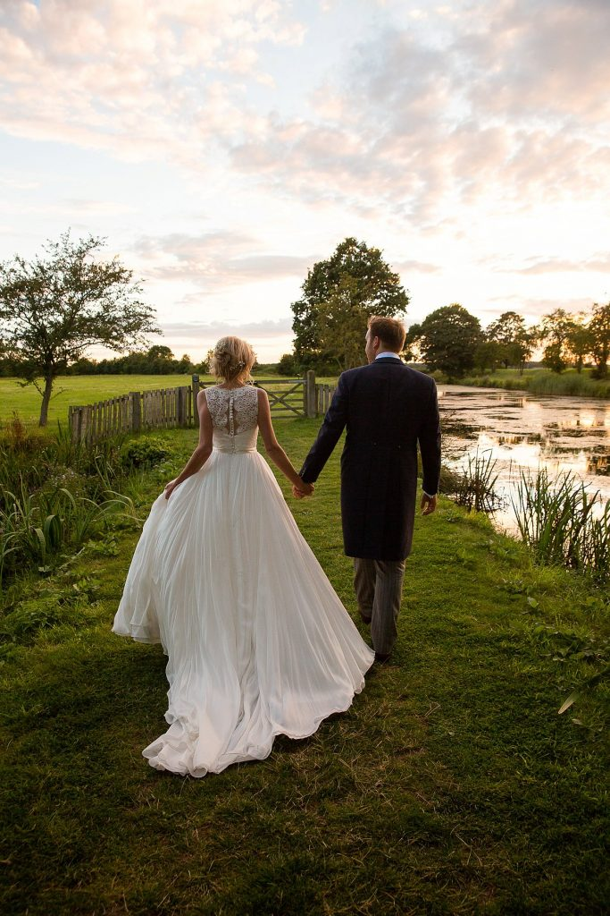 Bride and groom walk at sunset at Lyveden New Bield National Trust wedding by Mckenzie brown photography
