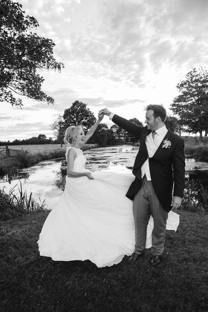 Bride spins round at Lyveden New Bield National Trust wedding by Mckenzie brown photography