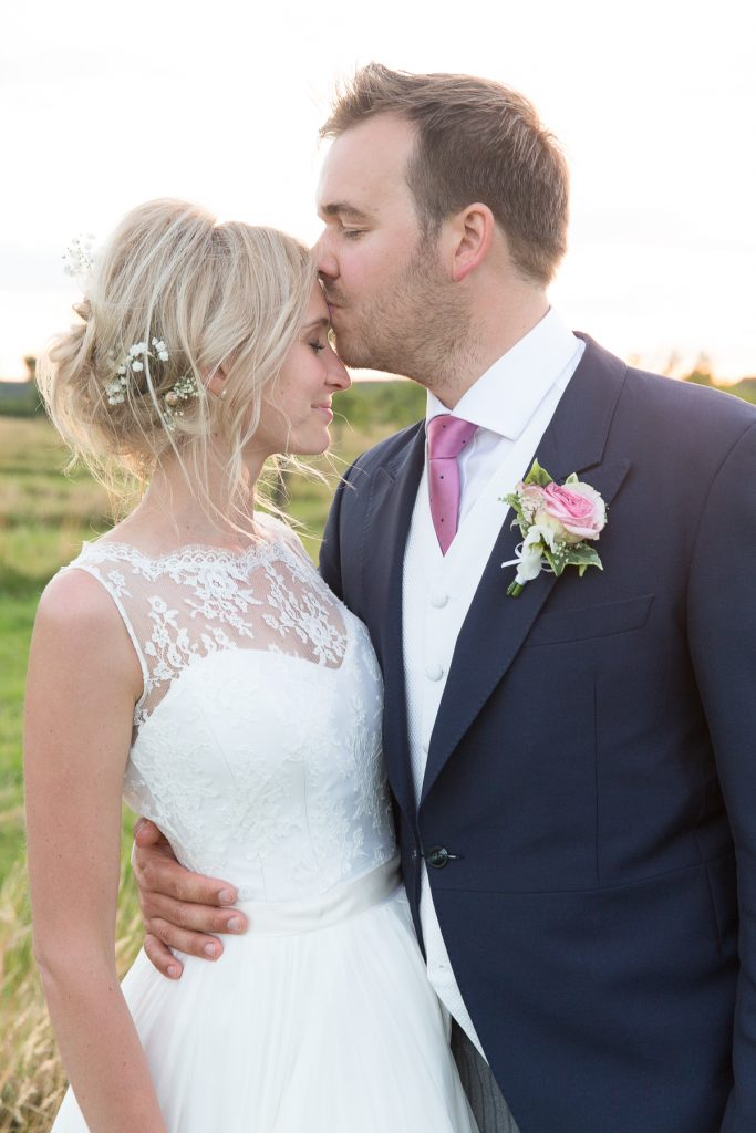 groom kisses brides head at Lyveden New Bield in Northamptonshire wedding photography