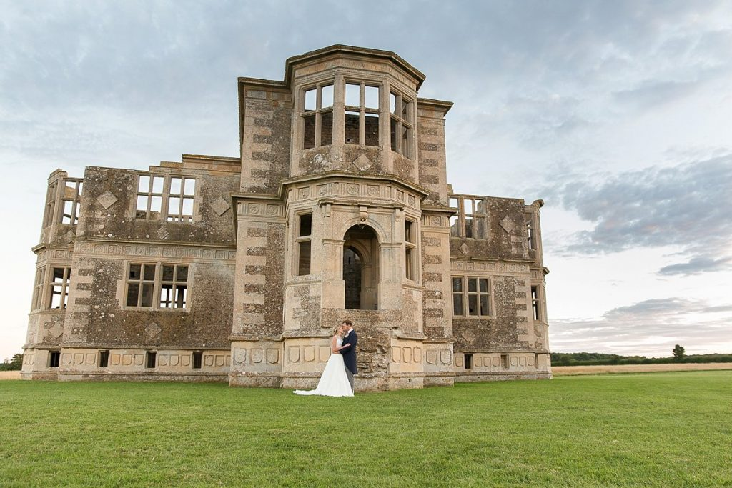 Bride and groom stand in front of Lyveden New Bield National Trust wedding by Mckenzie brown photography