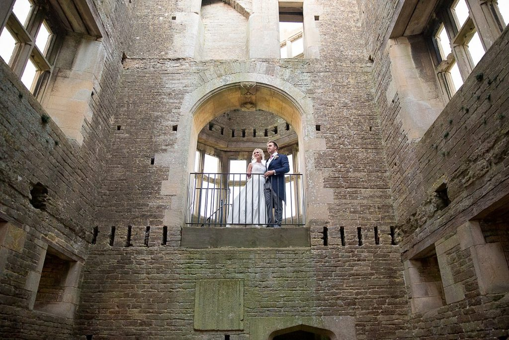 Bride and groom stand on platform inside Lyveden New Bield National Trust wedding by Mckenzie brown photography