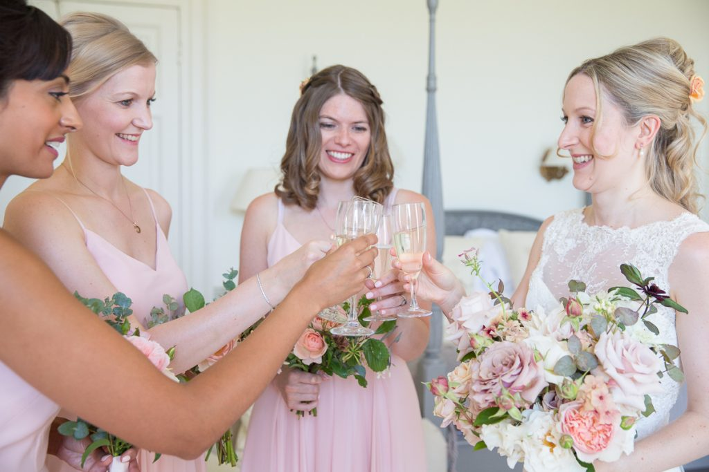 bridesmiads in pink toast the bride with champagne