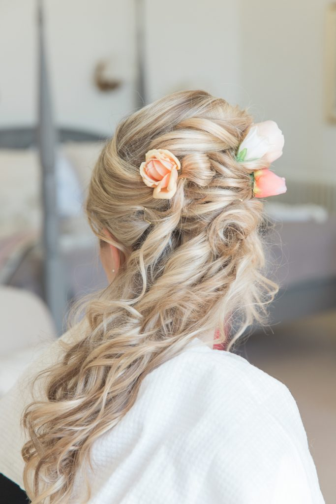 Close up of Bridal hair with peach flowers at Pynes House wedding in Devon by Mckenzie Brown Photography
