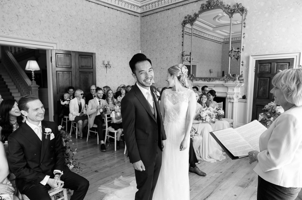 groom laughs towards the camera during the wedding ceremony at pynes house