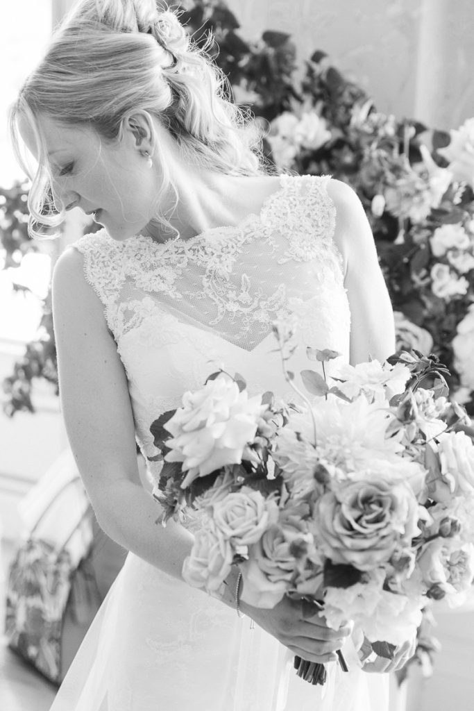 bride looks back to her dress holding a wedding bouquet