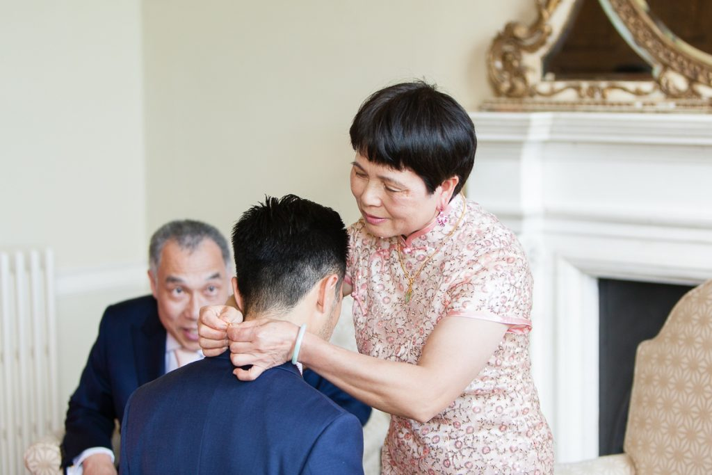 mother puts on necklace during traditional chinese tea ceremony at wedding