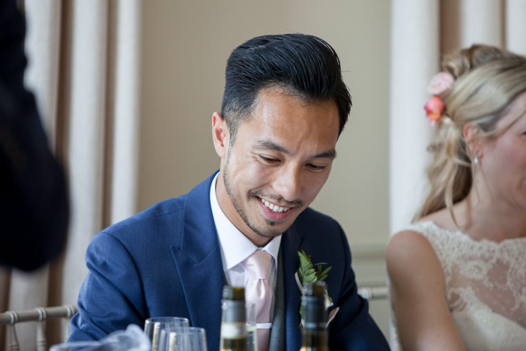 groom laughs during speeches at exeter wedding