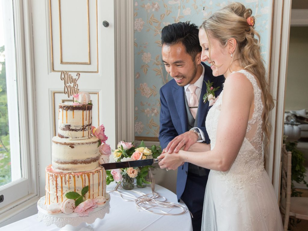 bride and groom cut wedding cake at Pynes House wedding Devon wedding photographer Mckenzie brown photographer