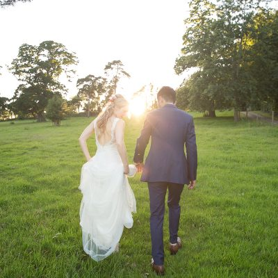 Couple walk through the gardens at Pynes House as the sun sets between them