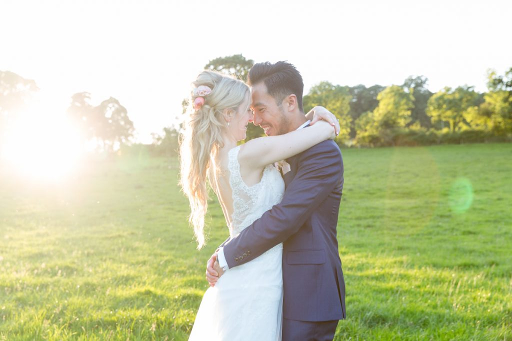 sun sets as bride and groom hug each other