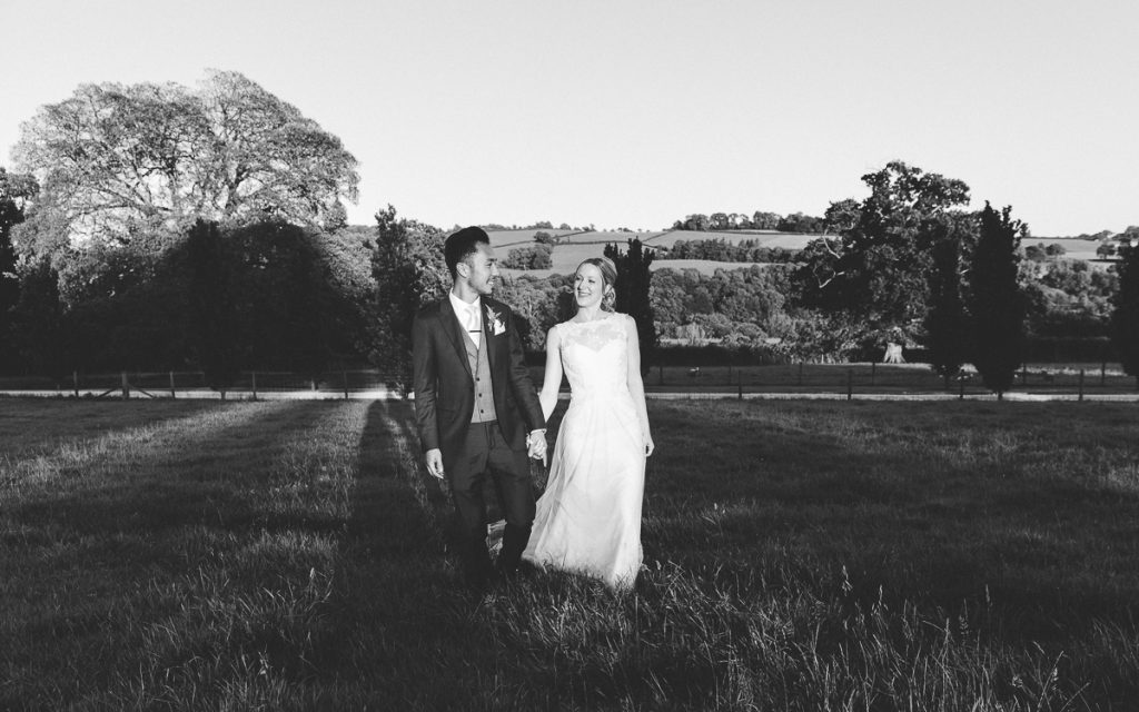 Bride and groom walk in gardens at Pynes House wedding in Devon by Mckenzie Brown Photography