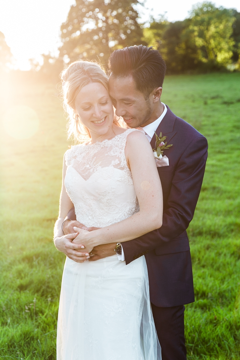 sun sets as wedding couple hug and laugh