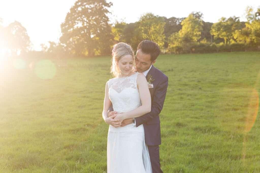 groom kisses brides shoulder as she smiles