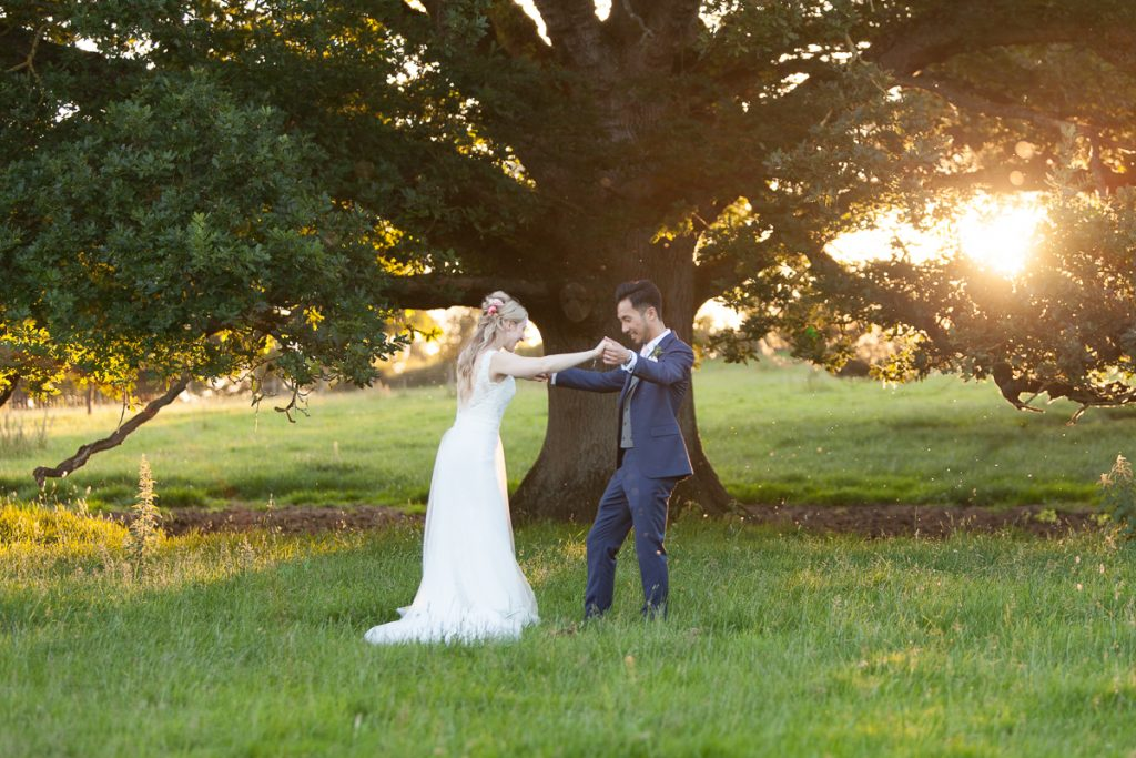Bride and groom hold hands in front of tree at Pynes House wedding in Devon by Mckenzie Brown Photography