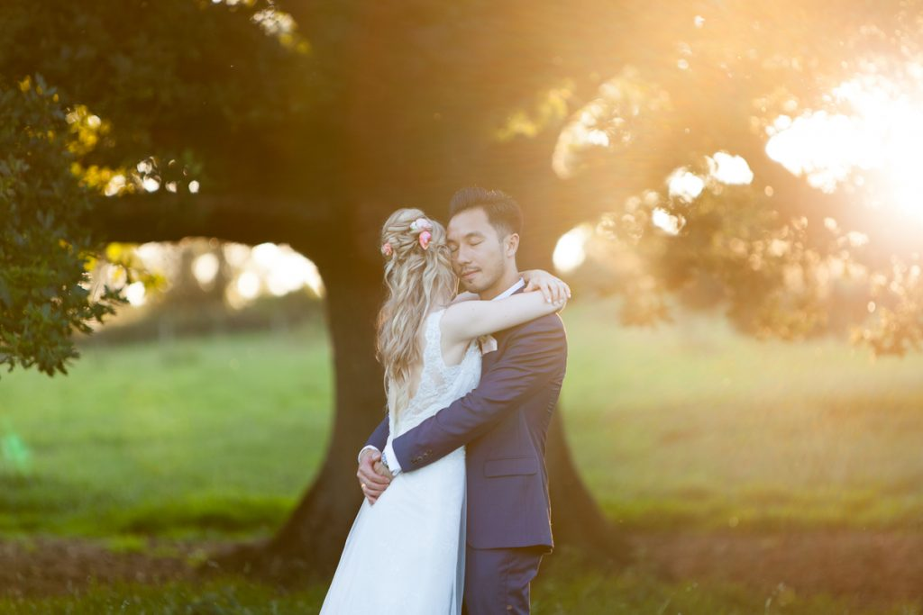 Bride and groom cuddle in gardens at Pynes House wedding in Devon by Mckenzie Brown Photography