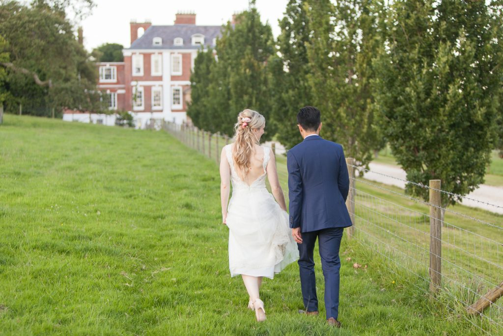 Bride and groom walking in front of at Pynes House wedding in Devon by Mckenzie Brown Photography