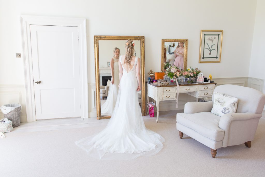 bride stands at Pynes House in bridal dress for her wedding