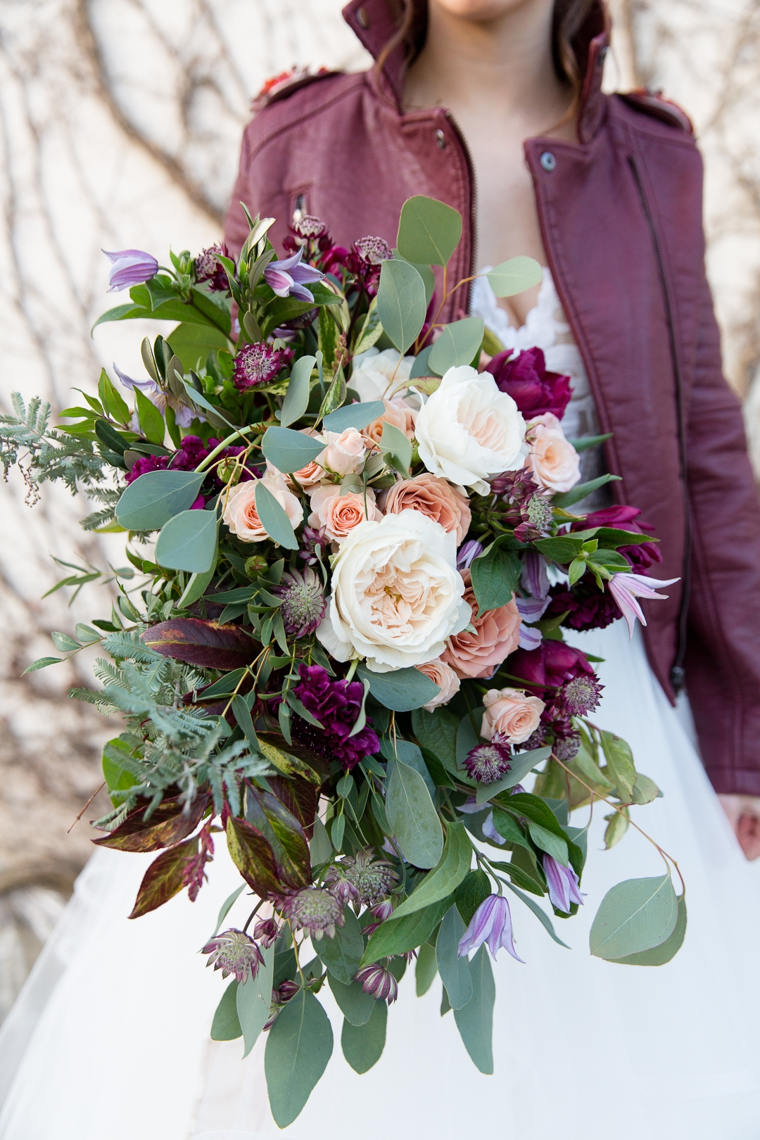 burgundy and blush wedding bouquet and leather jacket