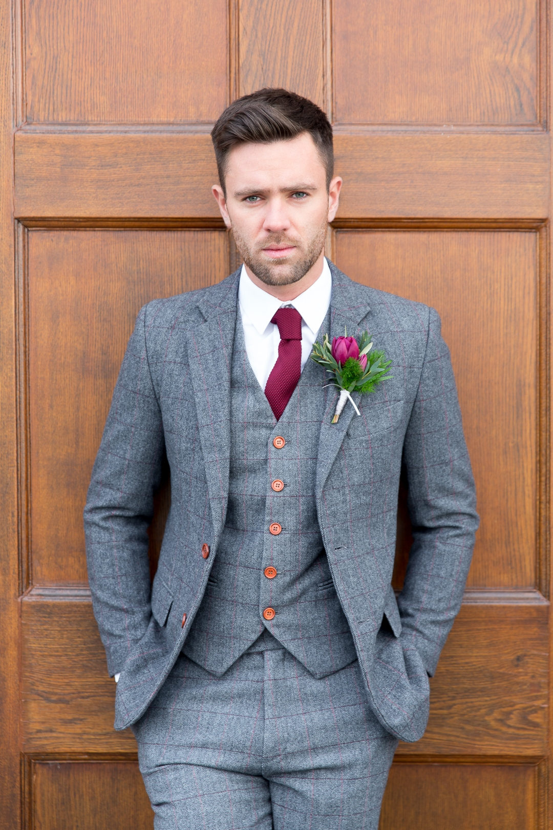 Groom with waistcoat and burgundy ties and button hole