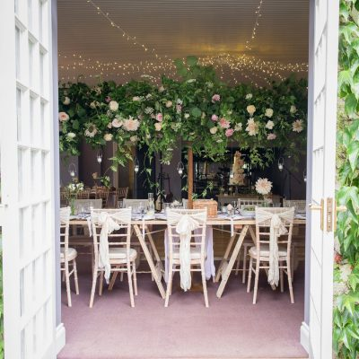 view through the doors into the orangery at Bridwell Park of wedding tables filled with flowers