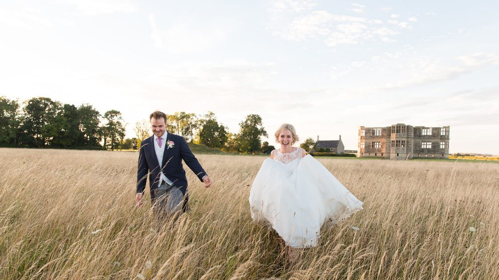 wedding couple ru through grass at Lyveden New Bield wedding