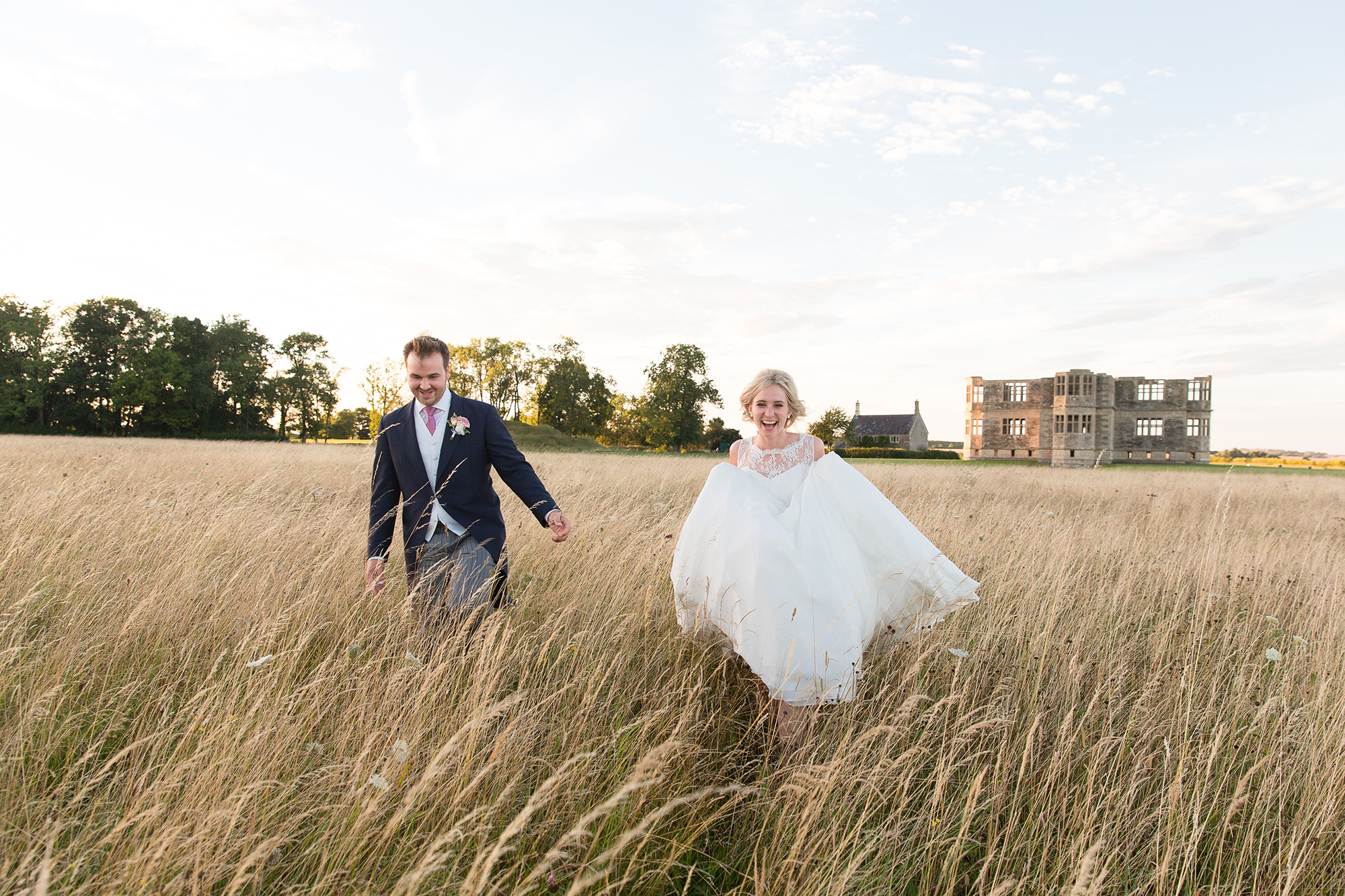 couple run through tall gras at Lyveden New Bield wedding