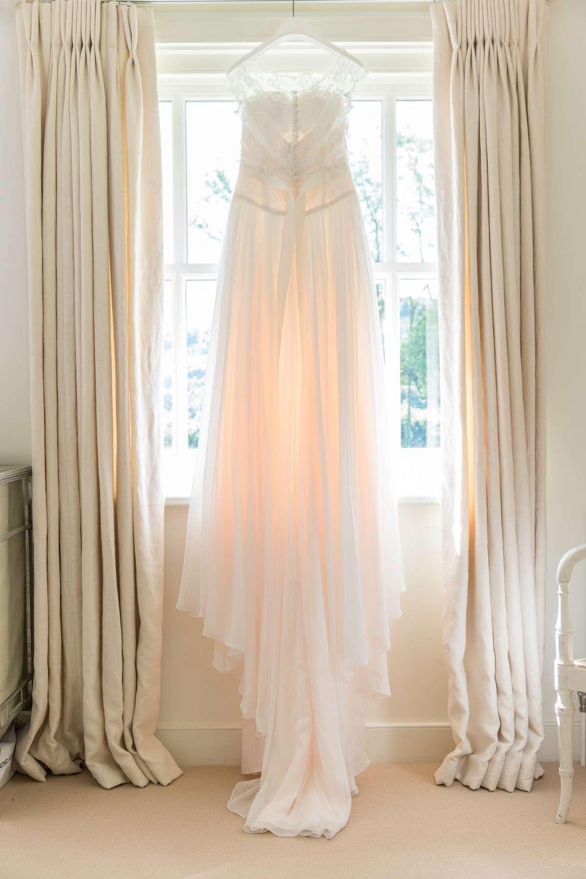 Naomi Neoh wedding dress hanging in window