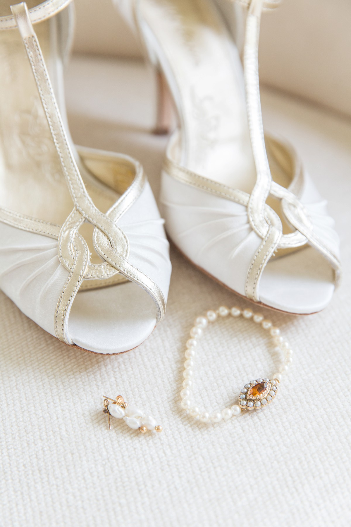 cream wedding shoe with pearl bracelet