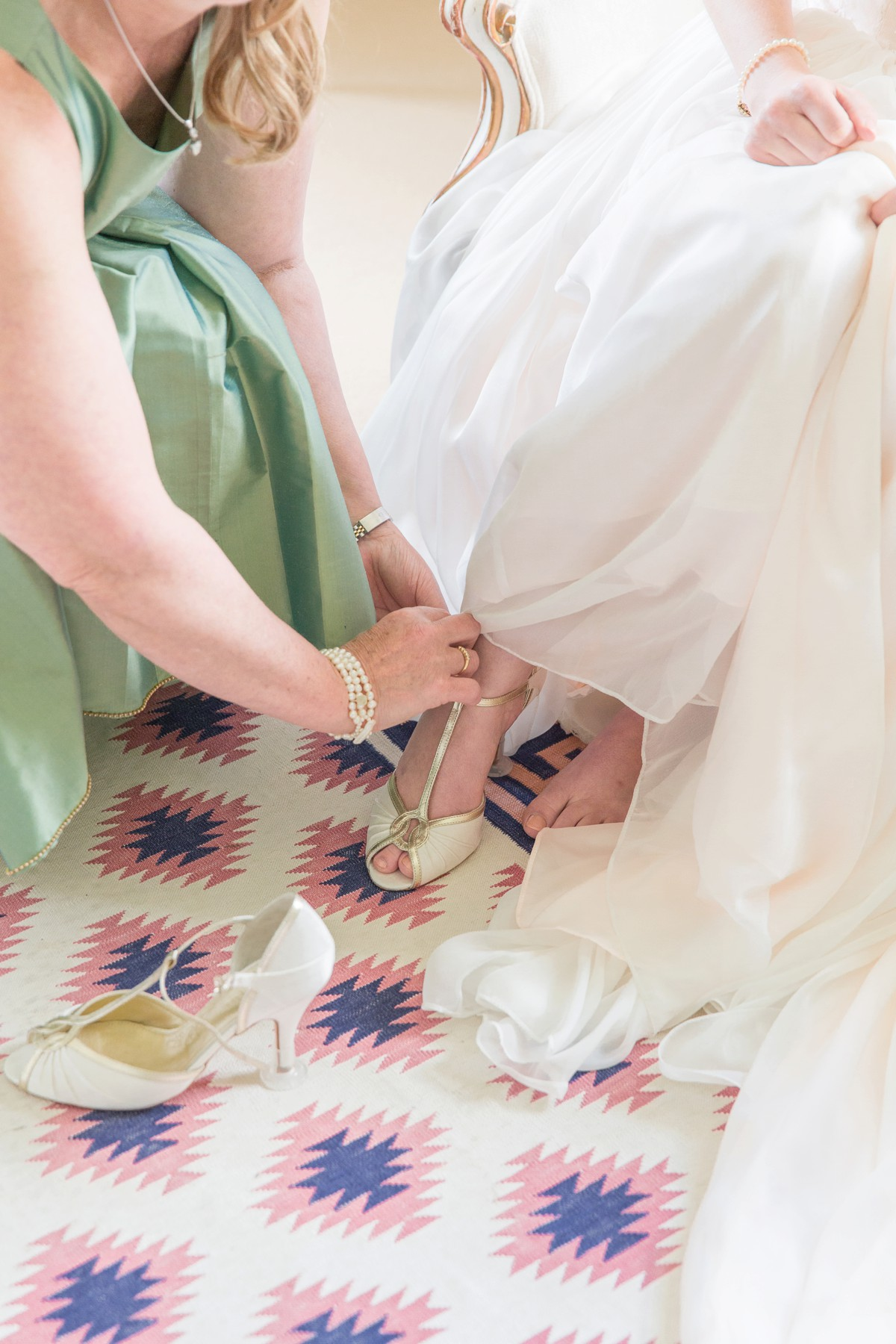 Mother of the bride putting wedding shoes on